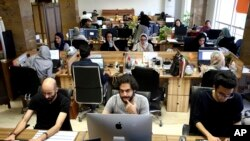 Snapp online taxi company work at their office in Tehran May 23, 2017 (AP Photo/Ebrahim Noroozi)