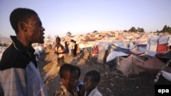 A man looks out over a tent city where many homeless Haitians are living in the wake of the disaster.