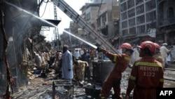 Пакистанские пожарные работают на месте взрыва на одном из рынков Пешавара. 29 сентября 2013 года.
