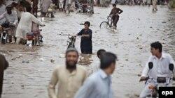 Пәкістанда 2015 жылы шілдеде тасқын су басқан жолмен кетіп бара жатқан адамдар. (Көрнекі сурет.)