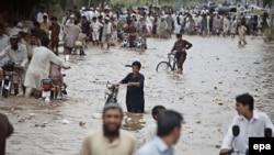 Люди ходят по затопленным дорогам в Пакистане в 2015 году. Иллюстративное фото.