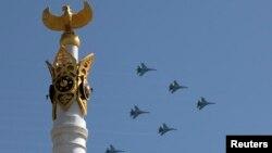 Военные самолеты кружат над небом Астаны во время парада в День защитника Отечества. 7 мая 2014 года.