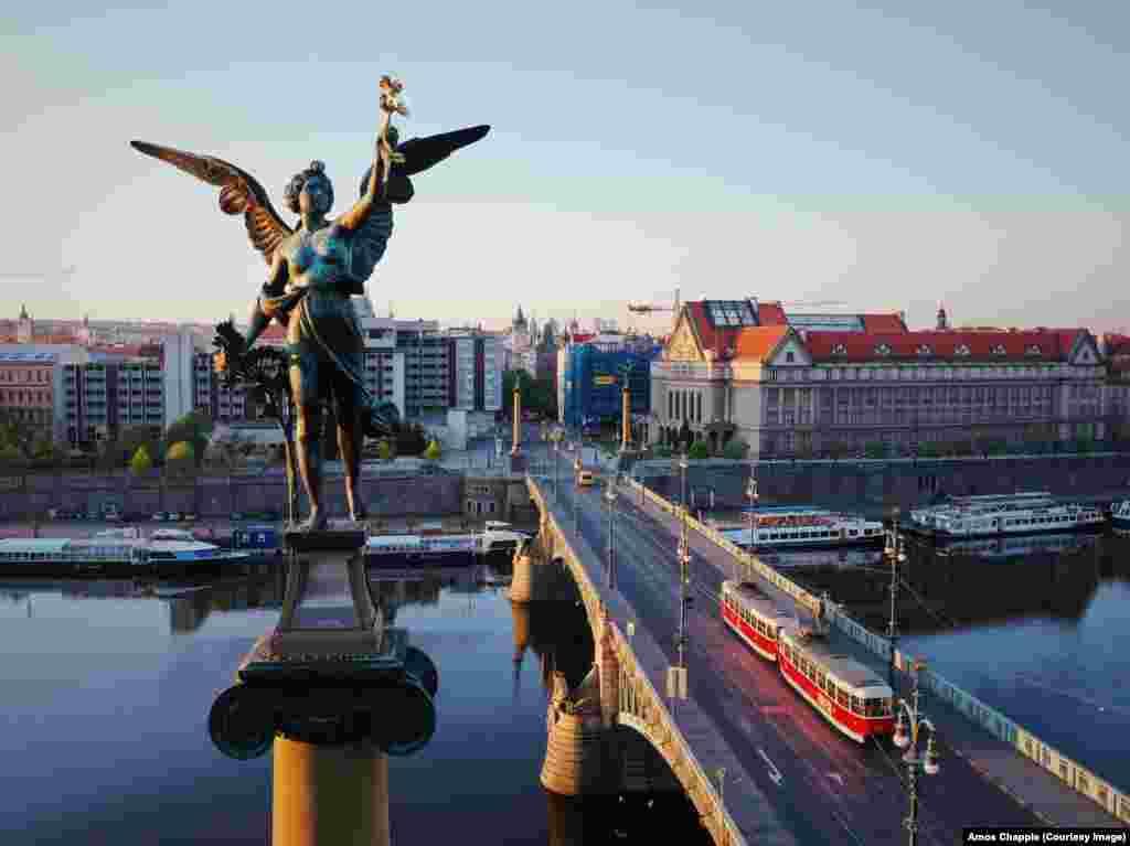 Сутрешното слънце осветява една от четирите крилати женски фигури, които украсяват Чехов мост. Скулптурите, създадени от Антонин Поп (1815-1915), държат позлатени венци в ръцете си.