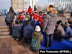 Тәуелсіздік ескерткіші алдында құран бағыштап отырған адамдар. Алматы, 16 желтоқсан 2019 жыл.