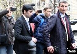 Руслан Шамсуаров (слева в костюме) покидает Гагаринский суд Москвы после приговора, 17 октября 2016 года