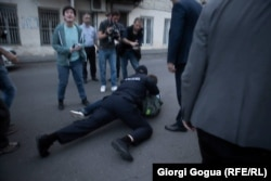 A police officer tackles a man who allegedly assaulted LGBT protesters in Tbilisi on May 17.