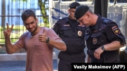 Pyotr Verzilov (left) gestures as he walks with police during a court hearing at a courthouse in Moscow on July 31.