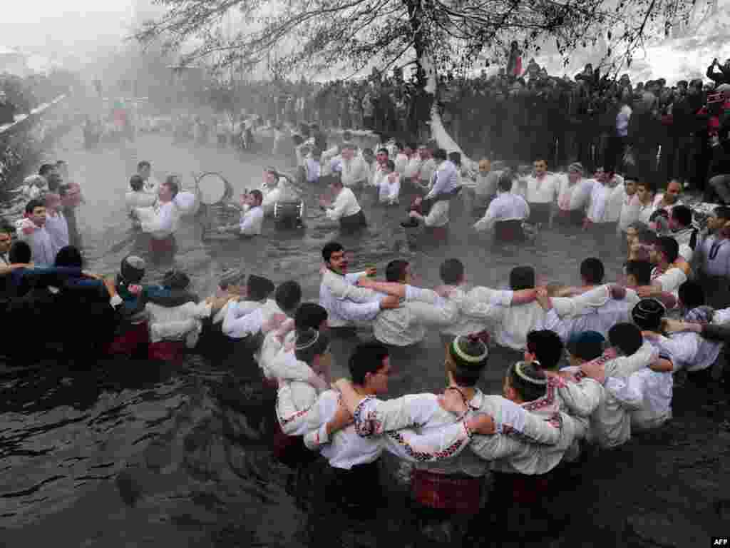 Bulgarian men perform the traditional Horo dance in the river Tundzha in the town of Kalofer. - Bulgarians also celebrate Epiphany Day in the water. According to tradition, whoever retrieves the cross from the water will be healthy throughout the year, as well as everyone who dances in the water.