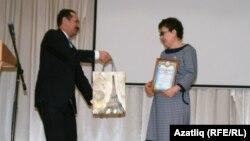 Илшат Насипов иң алдынгы укытучы Лилия Буранбаеваны бүләкли.