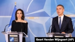 NATO Secretary-General Jens Stoltenberg (right) and Special Envoy for the United Nations High Commissioner for Refugees Angelina Jolie address the media after a meeting at NATO's headquarters in Brussels on January 31.