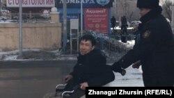 Полицейский увозит передвигающегося в коляске активиста Асанали Суюбаева в день задержаний десятков людей, выходивших на акцию протеста, к которым призвала оппозиционная группа. Актобе, 22 февраля 2020 года.