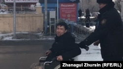 Disabled Kazakh activist Asanali Suyubaev being detained by police in Aqtobe in February