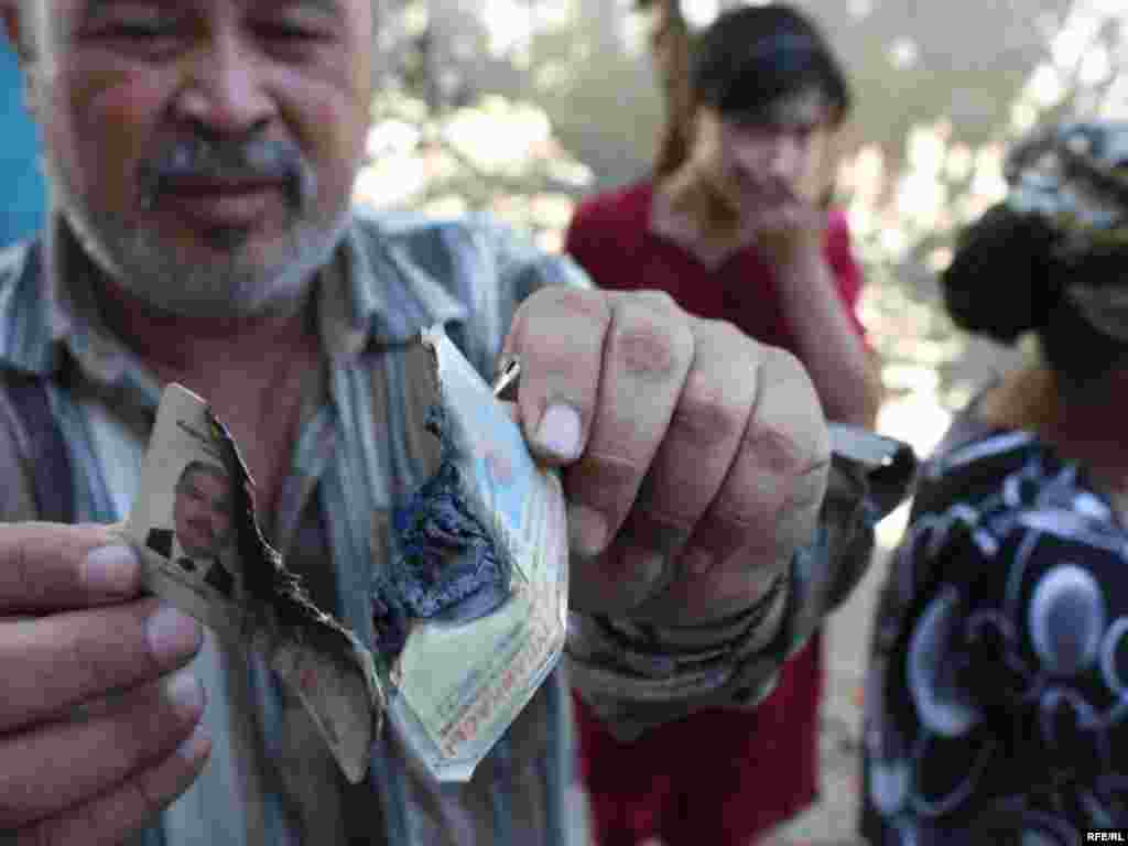 A resident of Nariman displays his passport, which he says troops destroyed during their raid. - Photo by Bruce Pannier