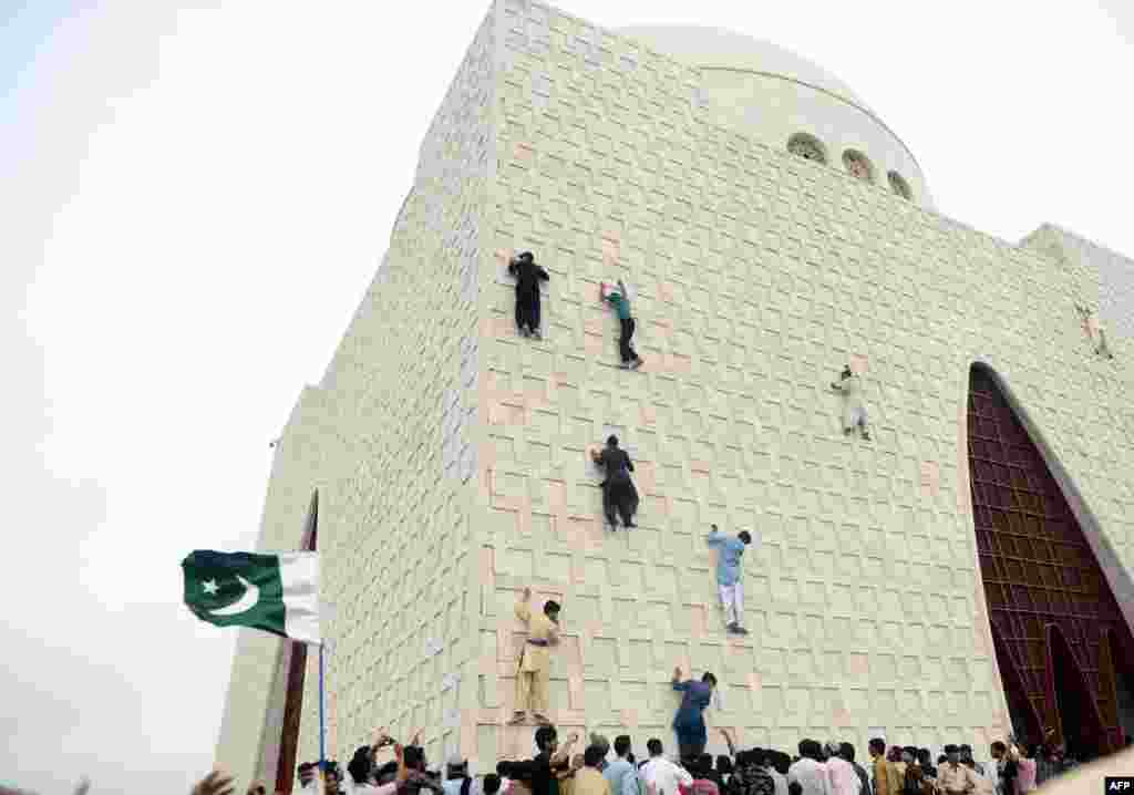 Pakistani youths climb the facade of the mausoleum in Karachi of Muhammad Ali Jinnah, who was the founding father of Pakistan, as they celebrate the country's 66th Independence Day. (AFP/Rizwan Tabassum)