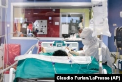 Медик пише записку для комуніації з пацієнтом, хворим на коронавірус в шпиталі Чініселло Бальзамо поблизу Мілана. 14 березня 2020 року