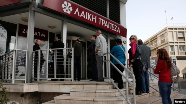 People line up to make a transaction at an ATM outside a branch of Laiki Bank in Nicosia, Cyprus, on March 21.