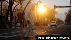 Сотрудник в защитном костюме на улице в Алматы. 30 марта 2020 года.