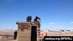 Астананың іргесіндегі Қоянды ауылына кіреберісте даулы жерге үй салып жатқан тұрғындар. Астана, 27 қазан 2014 жыл.