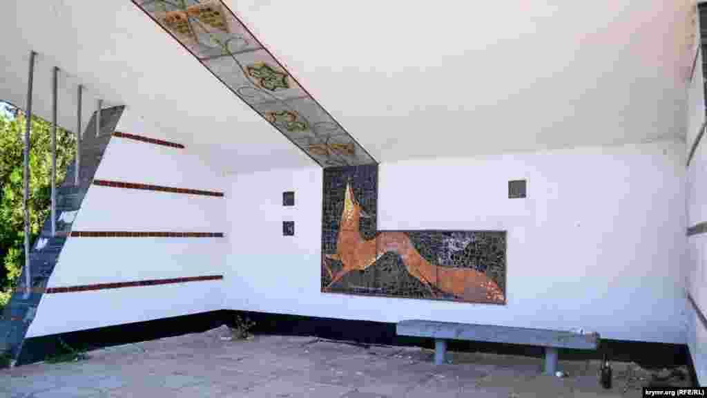 Внутри остановки – мозаичное панно с изображением лисы, виноградных листьев и гроздей. Прямо за остановкой– виноградники завода «Золотая балка»