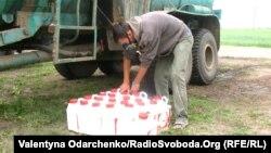 Працівник агрофірми заправляє комбайн отрутохімікатами