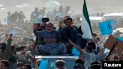 Abdullah Abdullah (in gray) sits atop a vehicle at an election rally in the Panjshir Province on March 31, 2014.