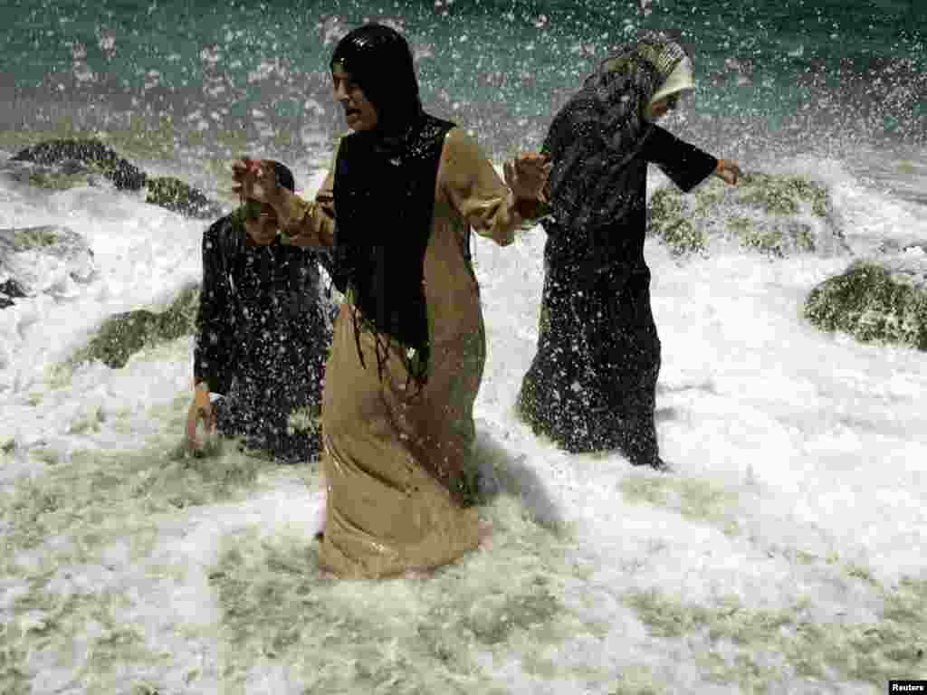Three women cool off on the beach at Algiers, June 4, 2006. REUTERS/Zohra Bensemra