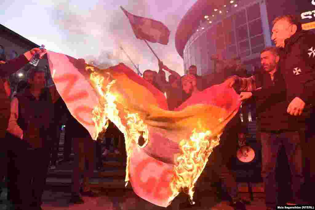 Демонстранты сжигают флаг ЛГБТ перед показом в Тбилиси.