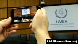 A person uses a smartphone to film the seat of the Director General of the International Atomic Energy Agency (IAEA) ahead of a board of governors meeting at the IAEA headquarters in Vienna, Austria July 25, 2019.