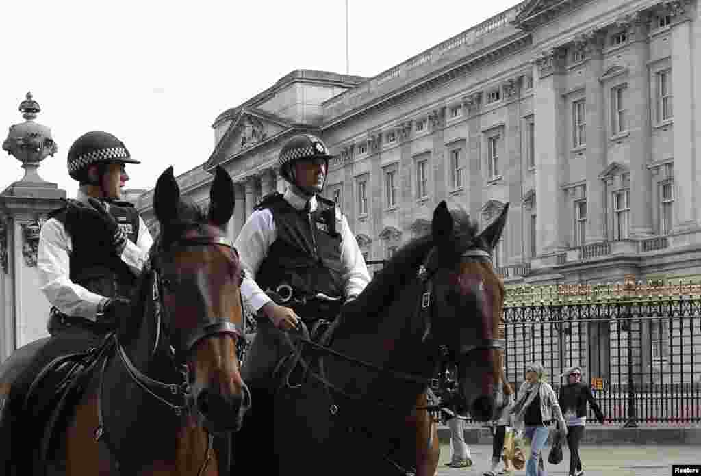 Mounted police officers patrol outside Buckingham Palace in London.