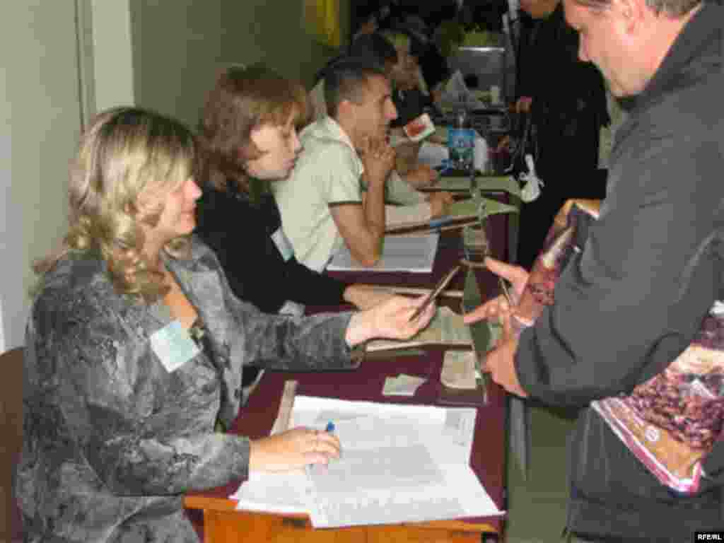 Election workers check voter-registration lists at a polling station in Donetsk