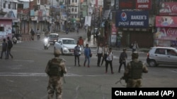 Indian paramilitary soldiers stand guard during a curfew like restrictions in Jammu on August 5.