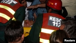 Rescue workers carry injured Pakistani cricketer-turned-politician Imran Khan, who is also chairman of the Pakistan Movement for Justice party, after he fell from a makeshift elevator during his campaign rally in Lahore on May 7.