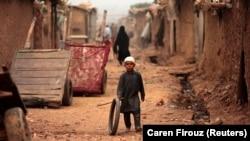 د اسلام اباد په کیمپ کې یو افغان ماشوم له ټایر سره لوبې کوي