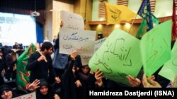 "Students holding hand-written signs in green – the color of the opposition movement-- against Hossein Shariatmadari, editor of the ultra-hard-line daily ""Kayhan,"" including one that read: ""The university is not a place for a lier"". 2014"