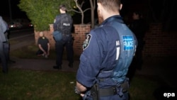 A man is arrested following the execution of search warrants in the northwest suburbs of Sydney on September 18.