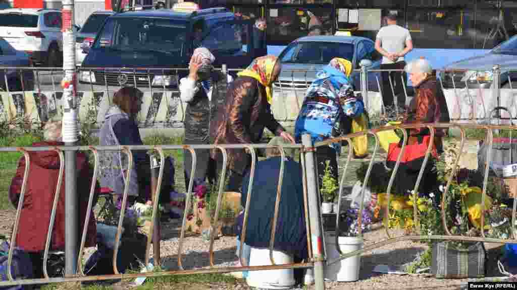 Торгующие цветами женщины одеты в куртки, потому что утром температура воздуха +10-12 градусов