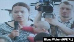 Камилла Пиралиева, одна из подсудимых по делу Серика Ахметова, с ребенком на руках. Караганда, 28 июля 2015 года.