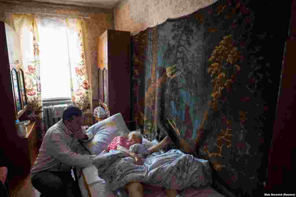Examining a patient at her home in the village of Ivankovichy. Rozumiy's patients are mostly very old or very young, with working-age adults seemingly avoiding the costs of medicines wherever possible.