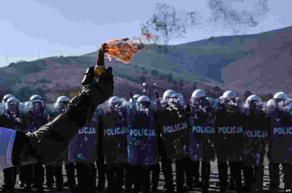 A riot policeman holds a Molotov cocktail as police and soldiers serving in the NATO-led peacekeeping force (KFOR) take part in a crowd and riot-control exercise near the village of Vrelo, Serbia. (AFP/Armend Nimani)