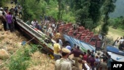 Locals and policemen gather around the bus as they rescue injured passengers from the damaged bus near the village Maroti, in Udhampur district of Jammu and Kashmir on May 11.
