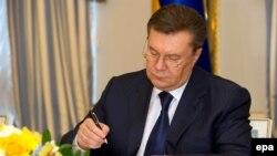 Президент Украины Виктор Янукович подписывает соглашение об урегулировании кризиса