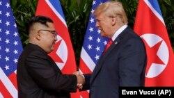 АҚШ президенті Дональд Трамп Солтүстік Корея лидері Ким Чен Ынмен қол асылып тұр. Сингапур, 12 маусым 2018 жыл.