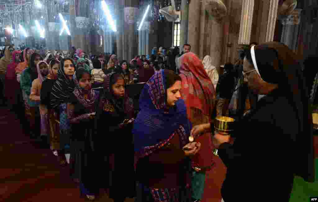 Pakistani Christians take communion during a Christmas Mass at St. Anthony's Church in Lahore on December 25. Pakistan is overwhelmingly Muslim and, with around 2 percent of the population, Christians are among the country's most marginalized citizens. (AFP/Arif Ali)