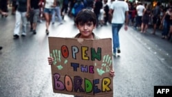 """Dijete drži transparent """"Otvorite granicu"""", Grčka"""