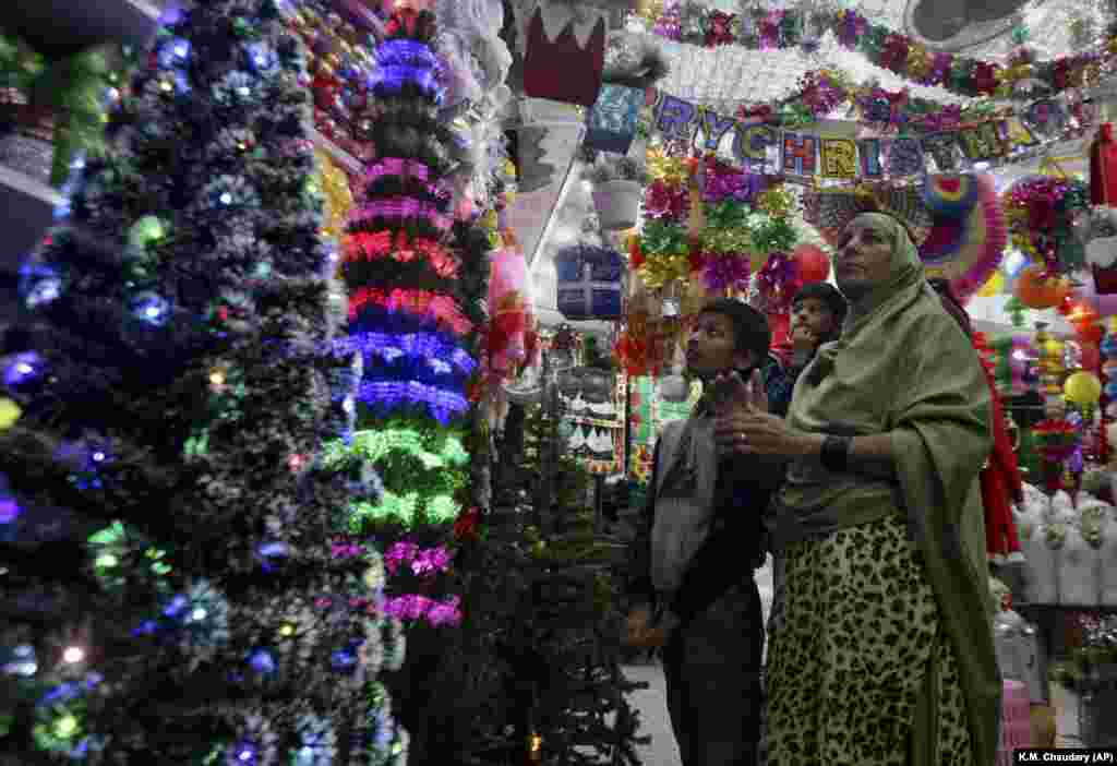 A Christian family browses Christmas ornaments to decorate their home for upcoming celebrations at a shop in Lahore, Pakistan. (AP/K.M. Chaudhry)