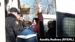 Azerbaijani journalist Khadija Ismayilova gestures to supporters at a court hearing earlier this year.
