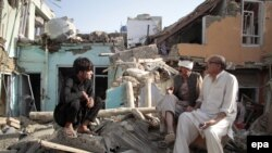 People survey their damaged houses at the scene of a bomb blast in Kabul on August 7.