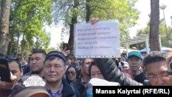 """Алматыдағы наразылық кезінде """"Нұр-Cұлтан менің астанам емес, АЭС-ке қарсымын, Дариға менің спикерім емес, Тоқаев менің президентім емес"""" деген плакат ұстап тұрған адам. 1 мамыр 2019 жыл."""