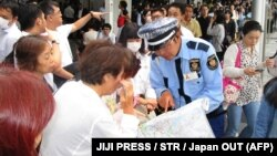 Сотрудник служб безопасности Японии инструктирует людей возле железнодорожной станции в Осаке после подземных толчков. 18 июня 2018 года.