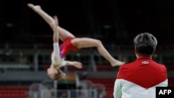 Rio-de-Žaneýroda orsýetli türgen artistik gimnastika boýunça tälim görýän sportsmene syn edýär. 4-nji awgust, 2016 ý.